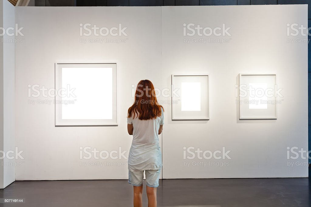 One woman looking at white frames in an art gallery stock photo