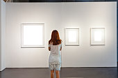 One woman looking at white frames in an art gallery