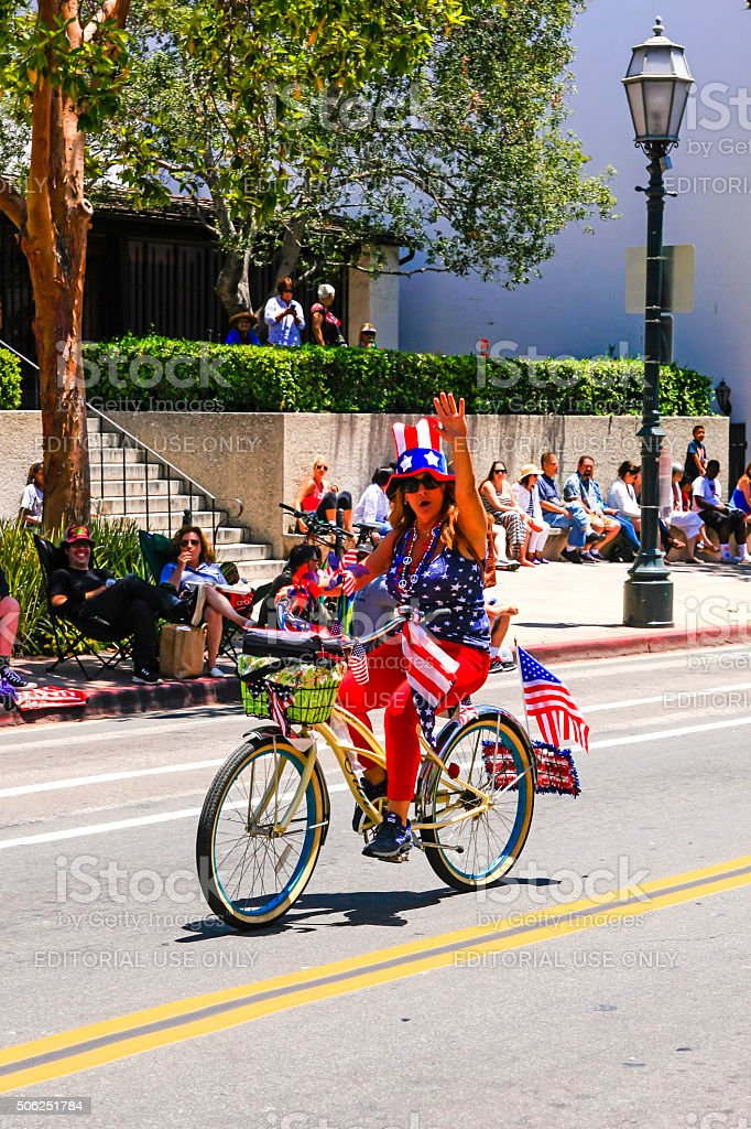 One woman riding bicycles on July-4th in Santa Barbara CA stock photo