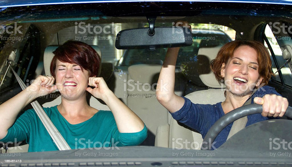 One woman singing and one woman covering her ears in a car royalty-free stock photo
