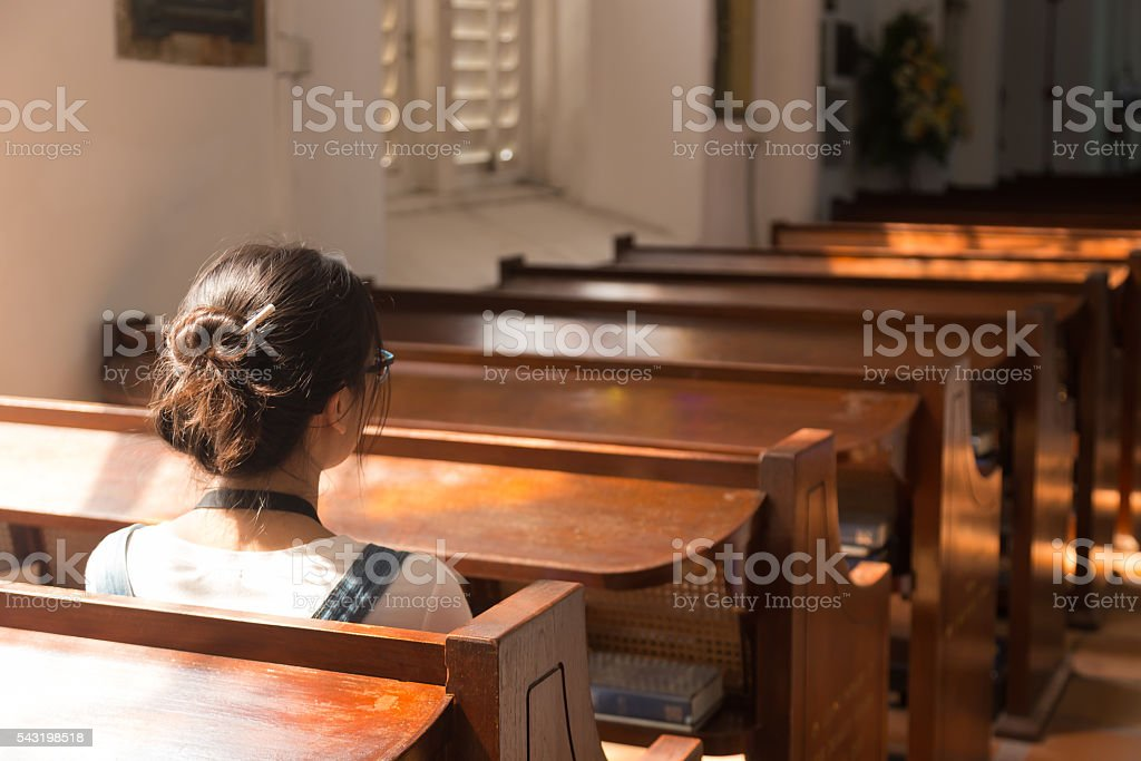 One woman sitting in church. stock photo