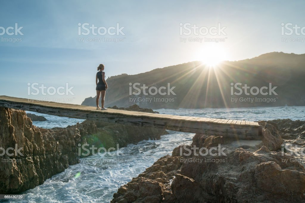 One woman standing on bridge over sea looking at sunset stock photo