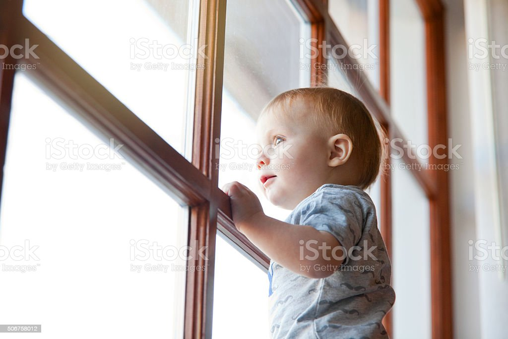 One Year Old Baby Boy Looking Out Window stock photo