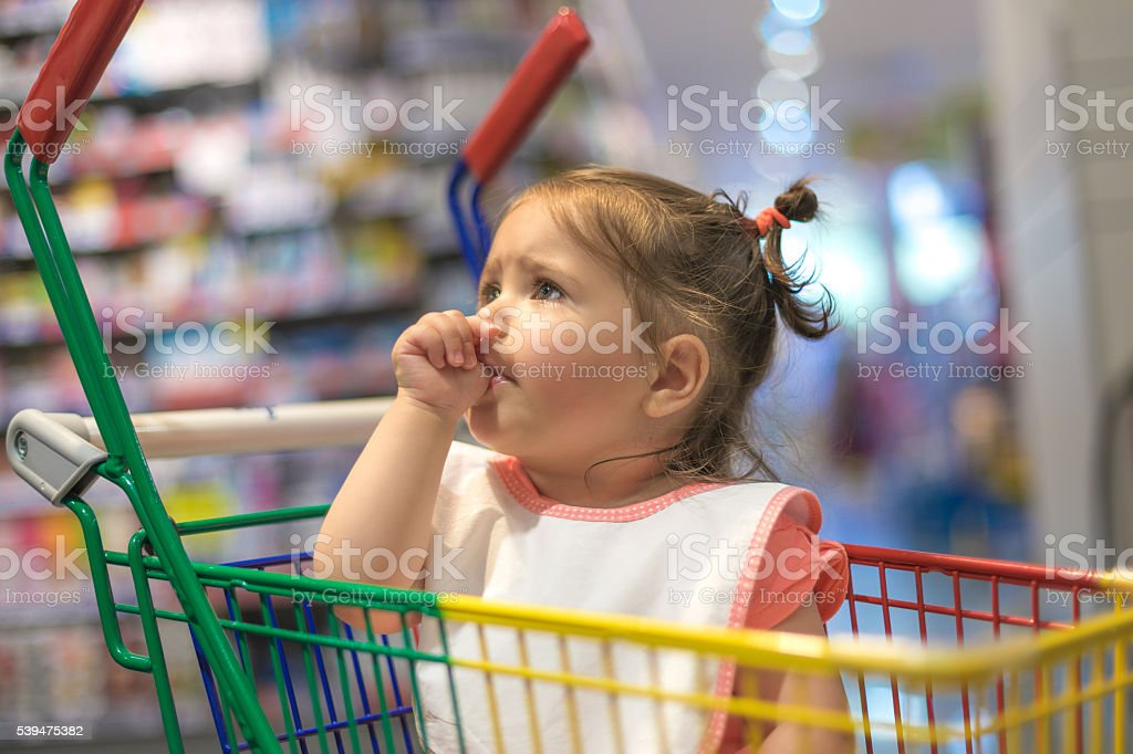 one year old baby in shopping cart stock photo