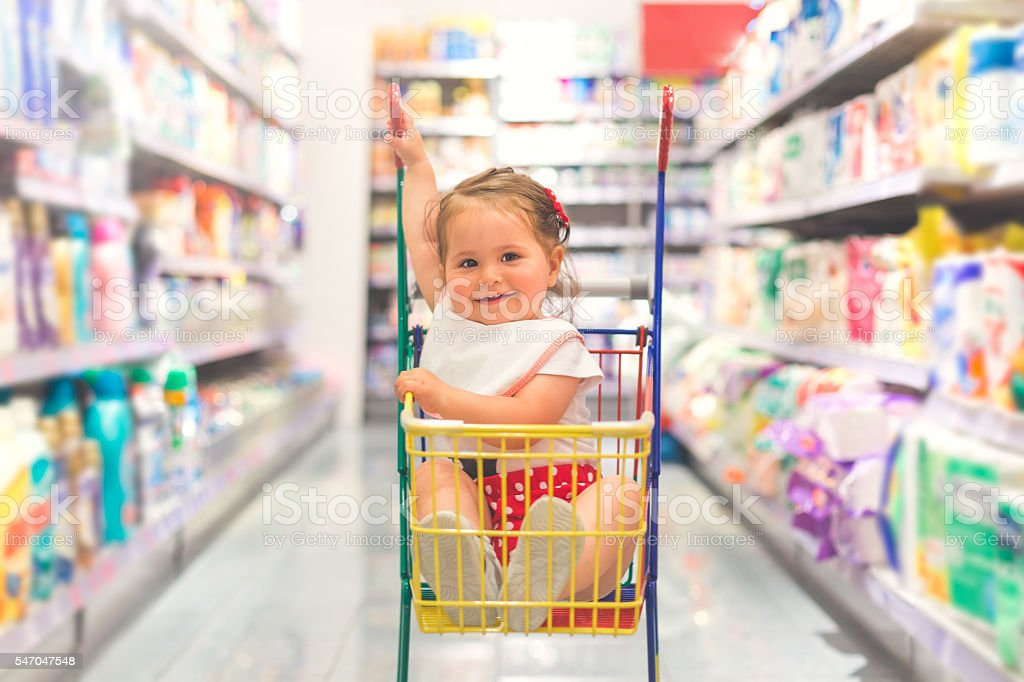 one year old baby sitting in a shopping cart stock photo