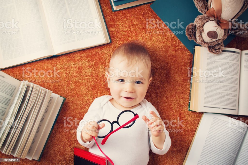 One year old baby with spectackles and a teddy bear stock photo