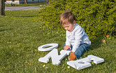 One year old boy looking at letters saying one