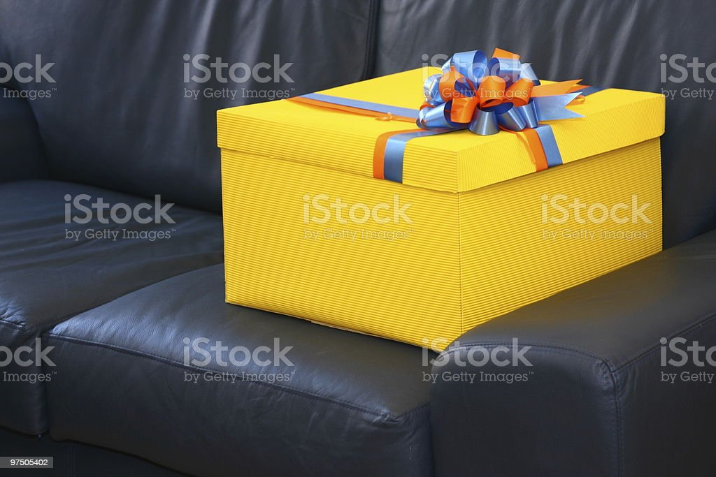 One yellow gift box on a blue leather sofa royalty-free stock photo