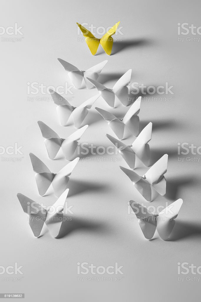 One yellow origami butterfly is leading white butterflies stock photo