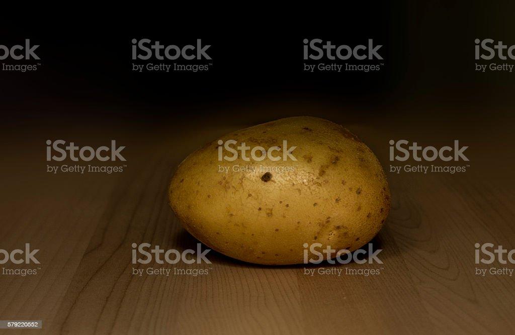 one yellow potato on wood stock photo