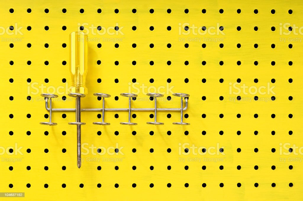 One yellow screwdriver sits in a rack on pegboard stock photo