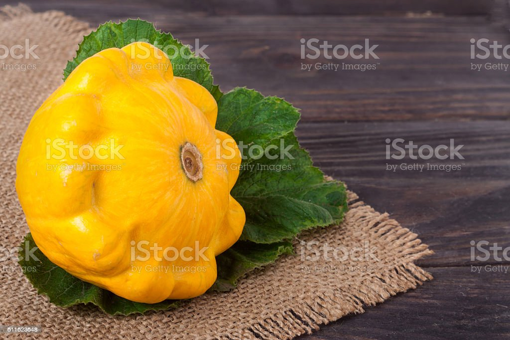 one yellow squash on a wooden background with napkin of stock photo