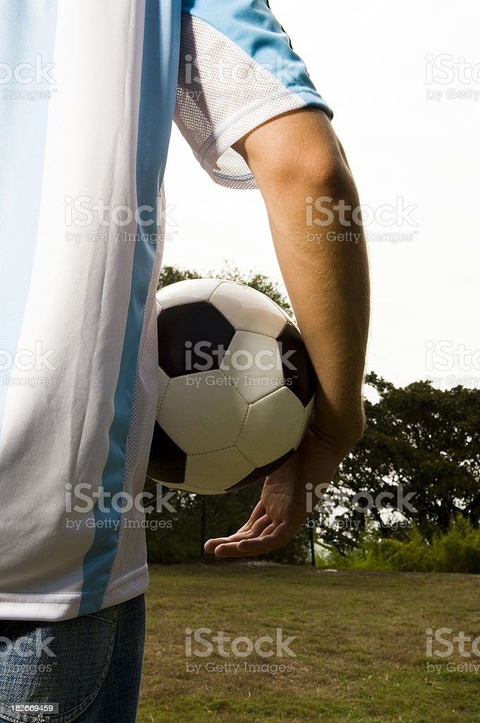 One young adult male wearing soccer t-shirts ball under arm. royalty-free stock photo