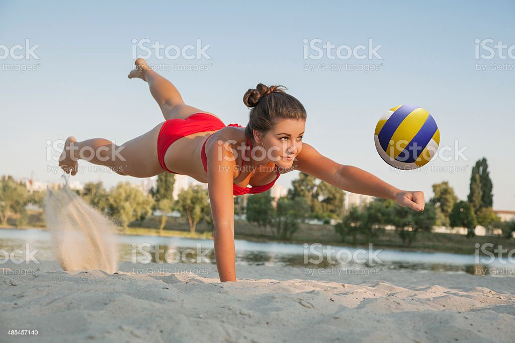 one young beautiful lady is playing volleyball on the beach stock photo