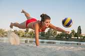 one young beautiful lady is playing volleyball on the beach