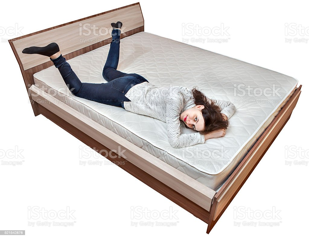 One young Caucasian woman relaxing on spring mattress wooden bed stock photo