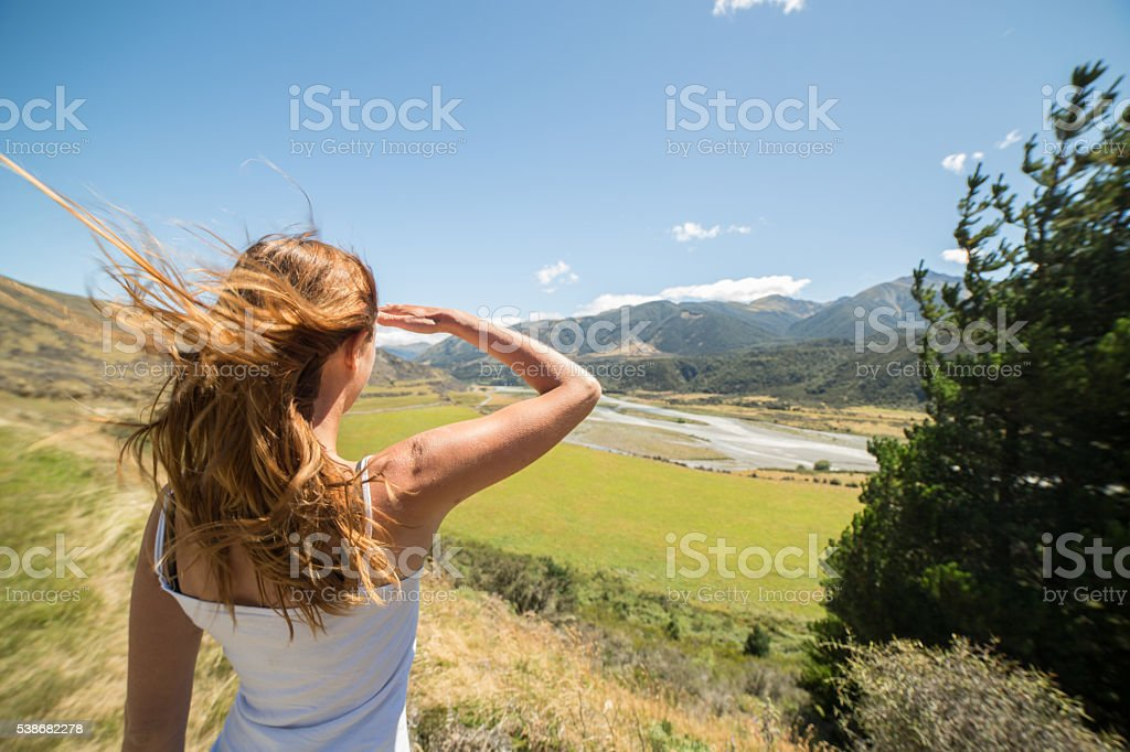 One young female stands on hill, looks at view stock photo