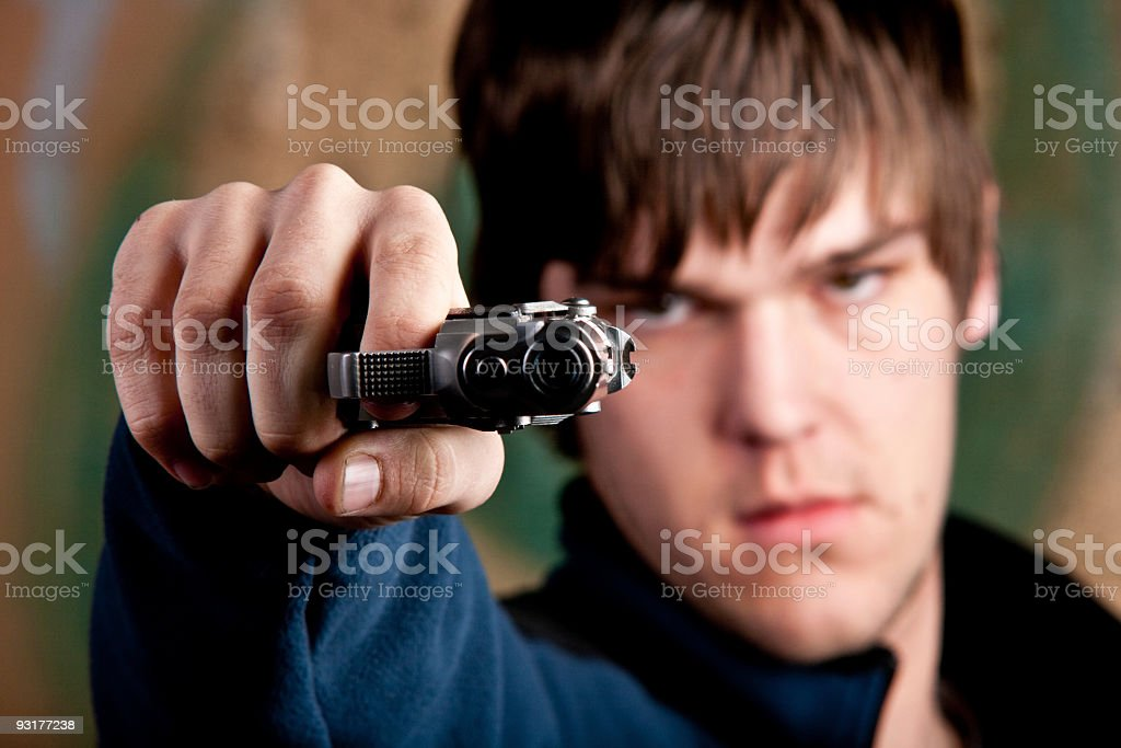 One young man aiming handgun at camera stock photo