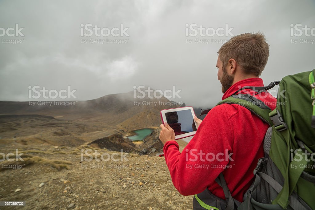 One young man hiking uses a digital map stock photo