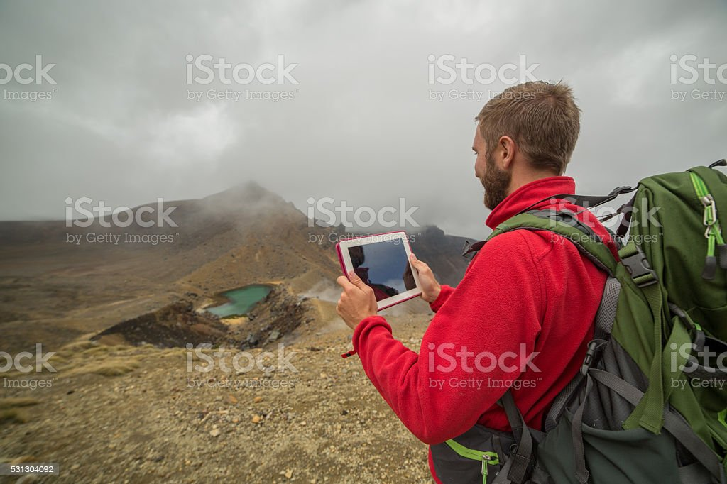 One young man hiking uses a digital map-New Zealand stock photo