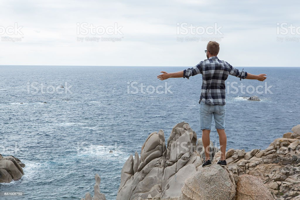 One young man standing on cliff above sea arms outstretched stock photo