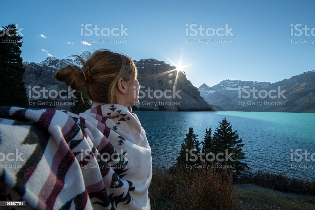 One young woman arms outstretched by the lake at sunset stock photo