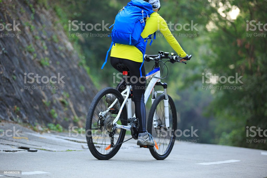 one young woman cyclist riding mountain bike on forest trail stock photo