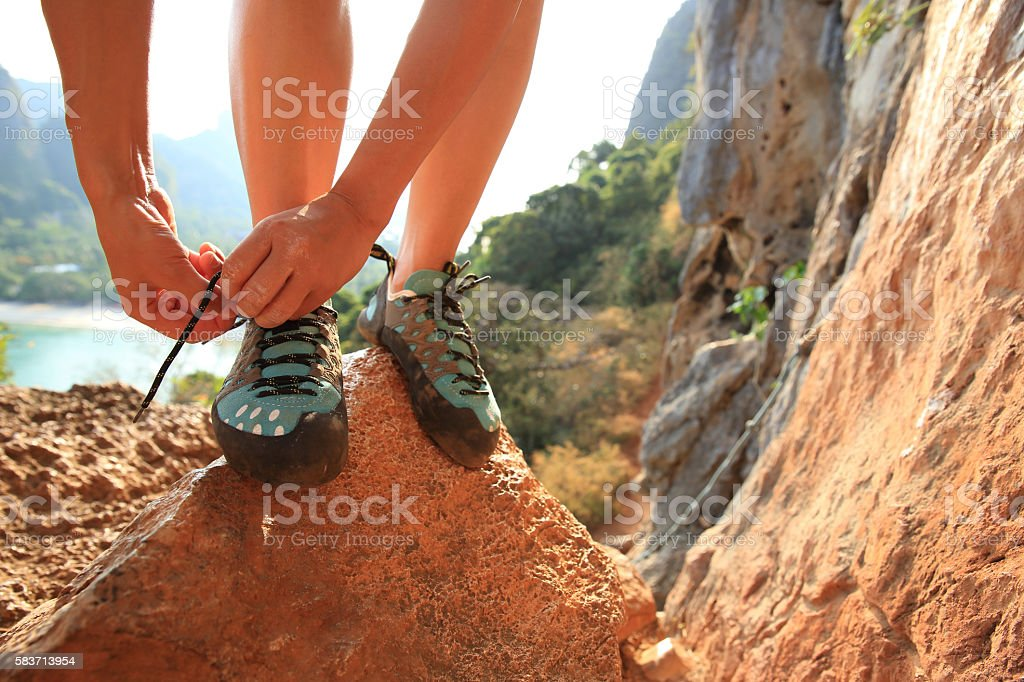one young woman rock climber tying shoelace on rock stock photo