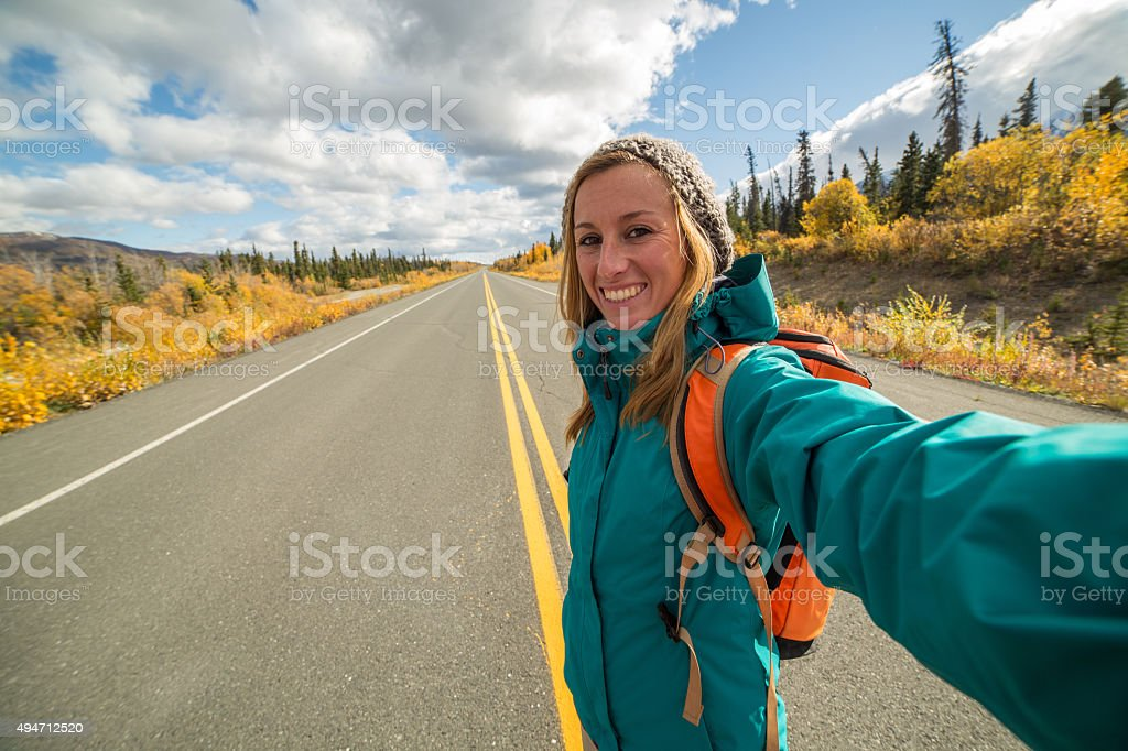 One young woman traveling taking selfie on the road stock photo