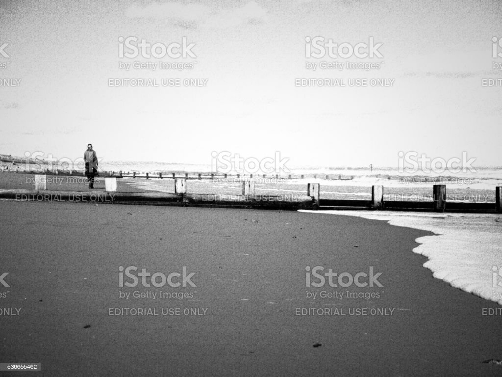 One Young Woman Walking on Aberdeen Beach, UK. stock photo