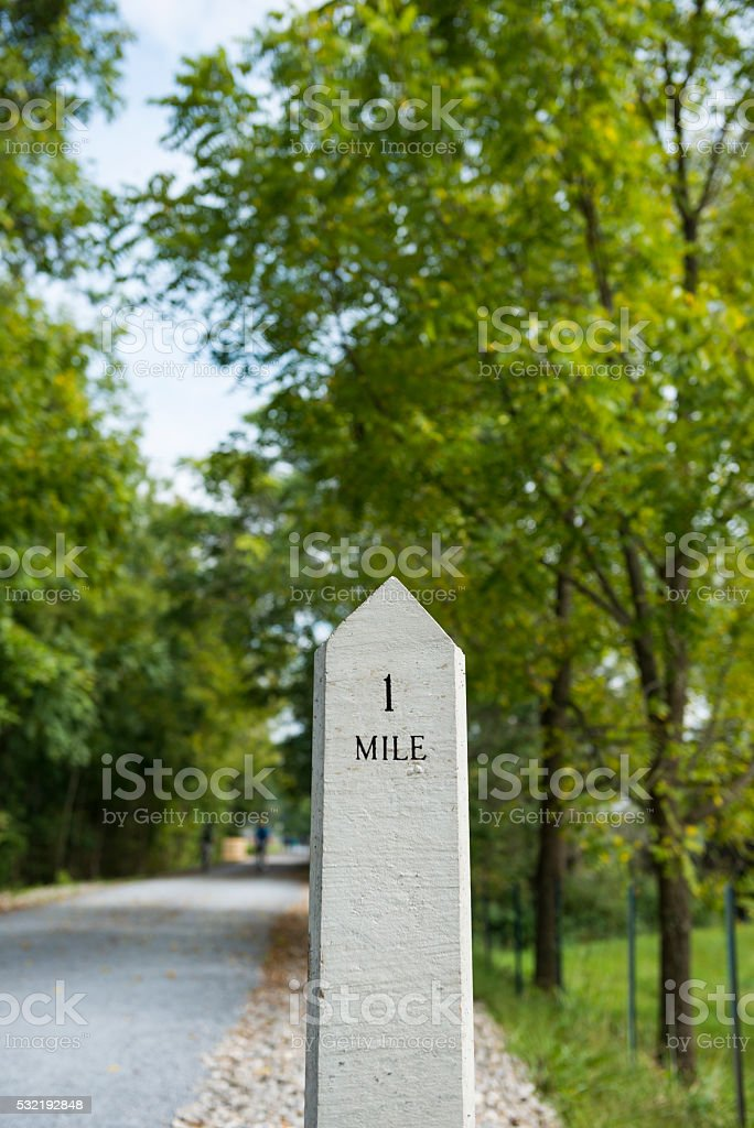 One-mile marker on trail in nature stock photo