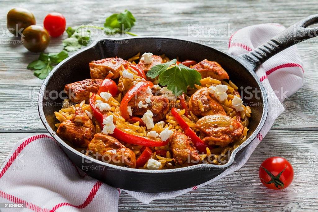 One-pot chicken fillet and orzo pasta with red bell peppers stock photo