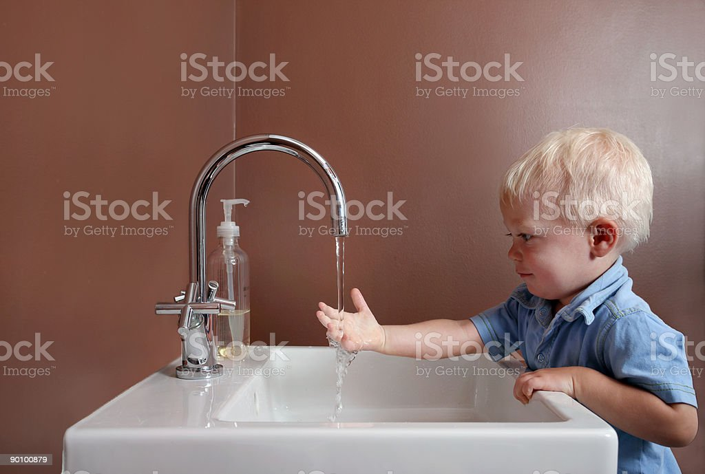 One-year-old boy washing hands. stock photo