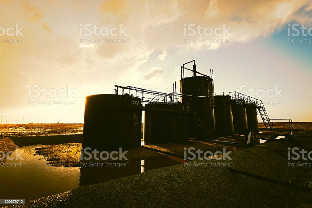 On-farm oil storage tanks after rain with stormy sunset stock photo