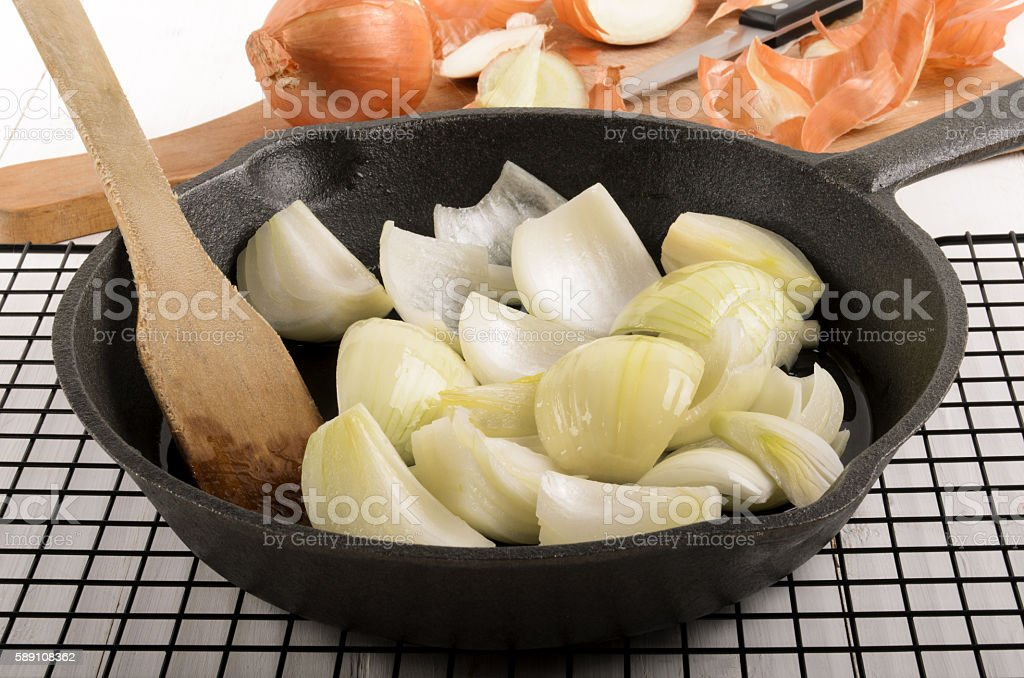 onion chunks with sunflower oil in a cast iron pan stock photo