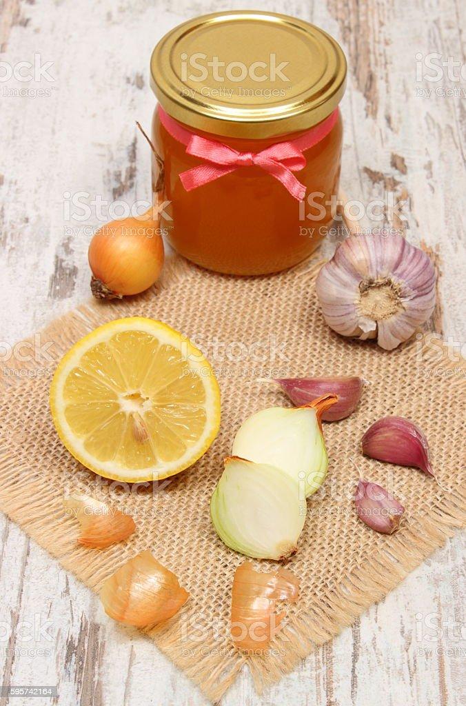 Onion, garlic, lemon and honey in glass jar, healthy nutrition stock photo