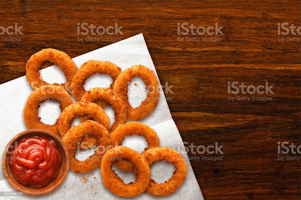 Onion Rings on Wax Paper with Ketchup on Dark Wood stock photo