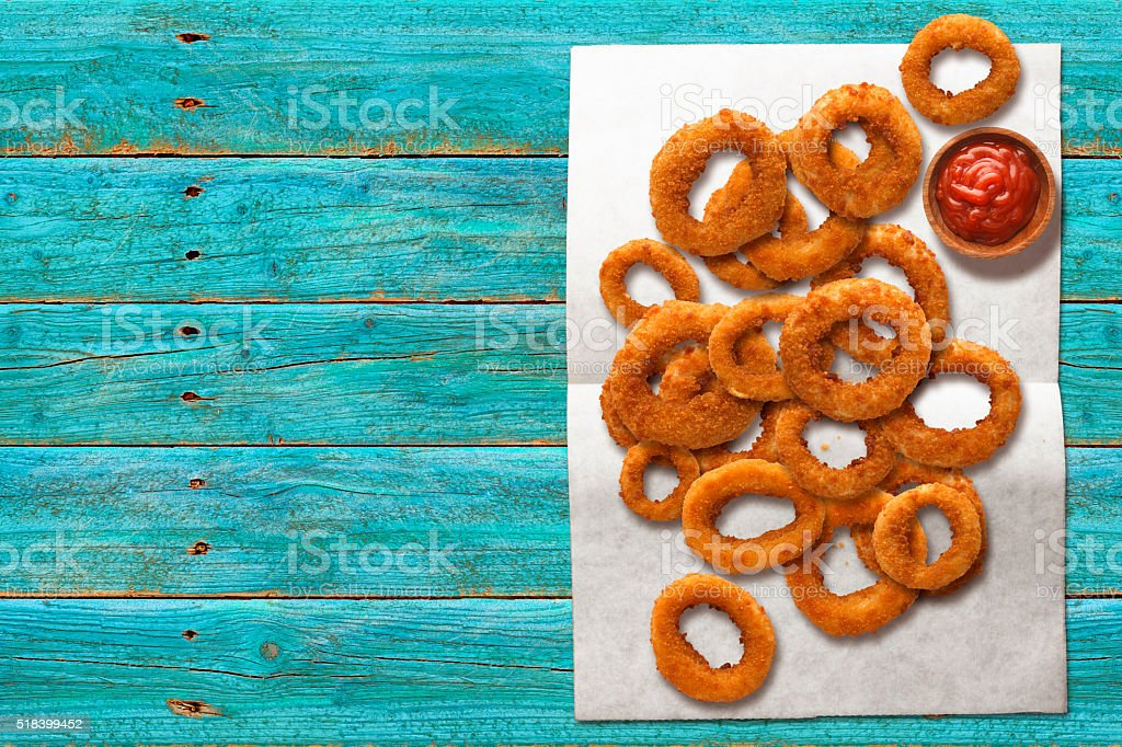 Onion Rings on Wax Paper with Ketchup stock photo