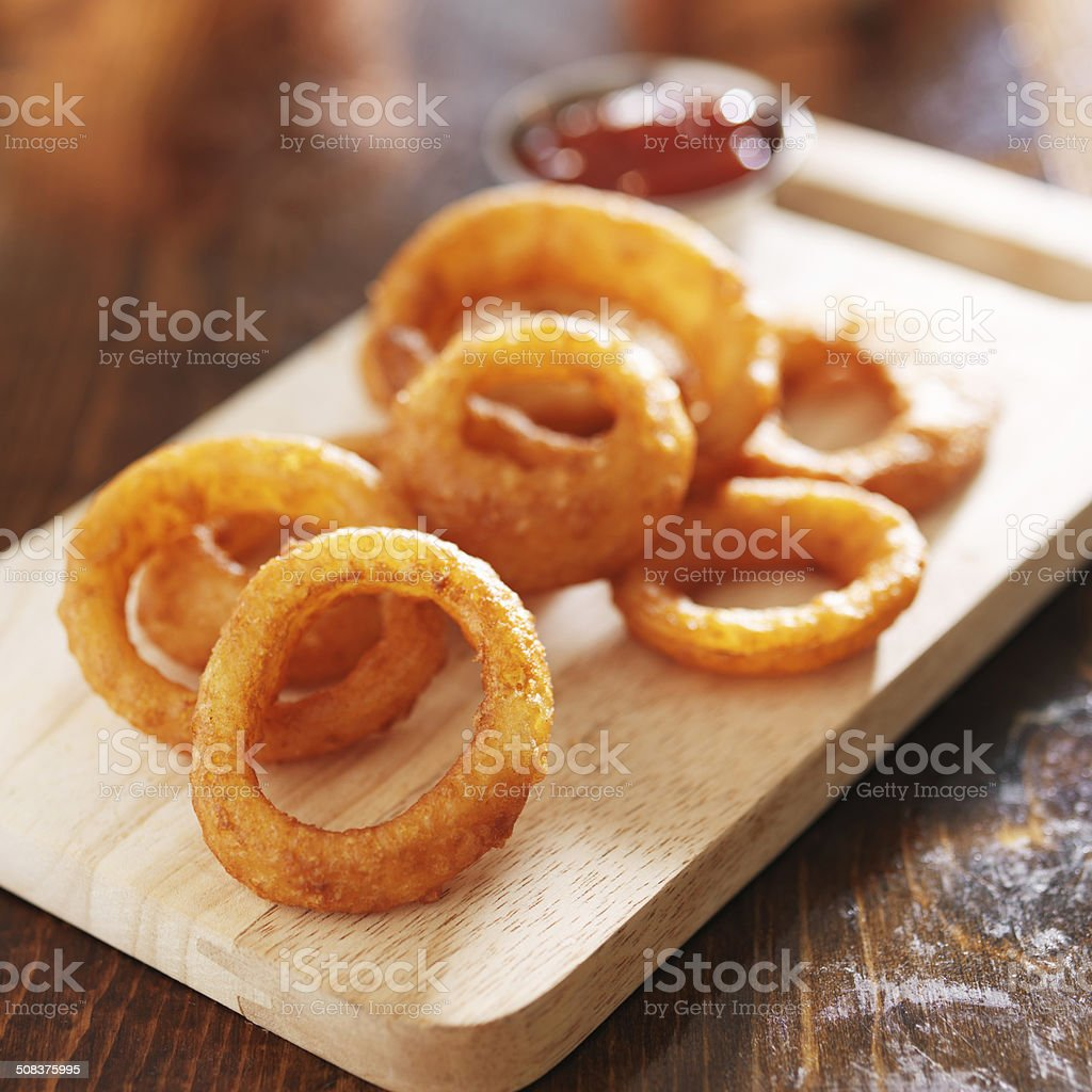 onion rings on wood board stock photo