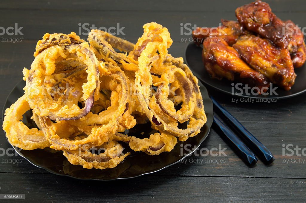 onion rings with chopsticks and bbq chicken wings stock photo