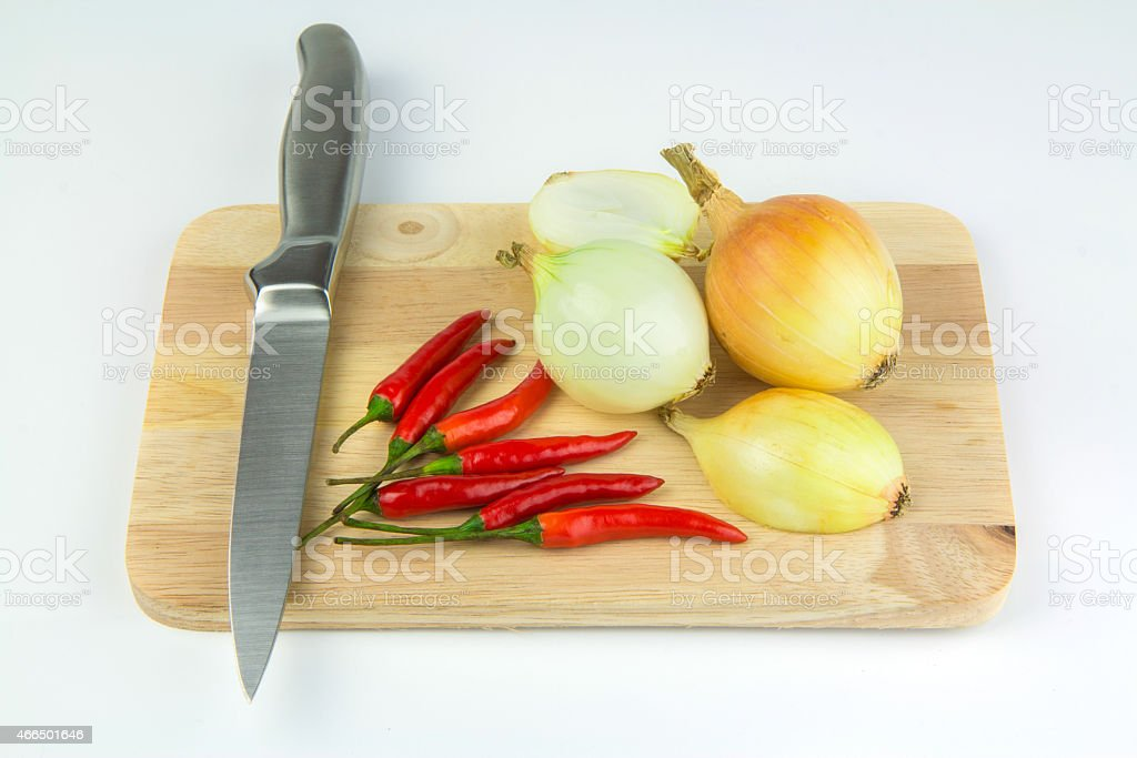 Onions and chillies on chopping board royalty-free stock photo