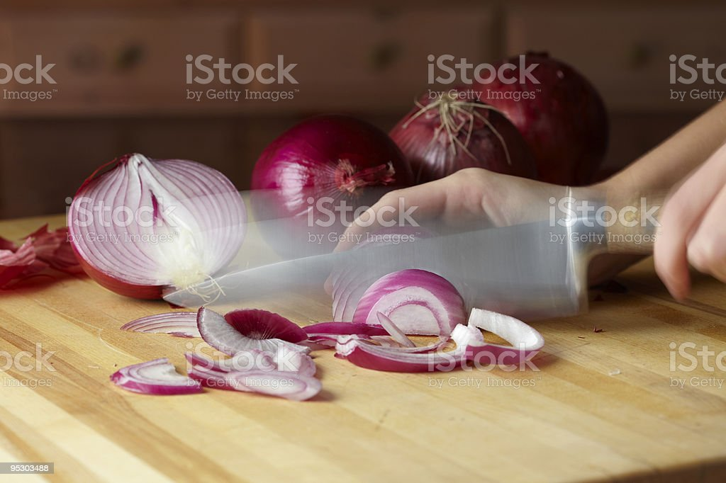 Onions being sliced in motion stock photo