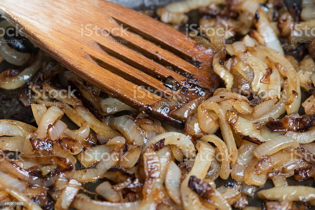 Onions caramelizing in frying pan stock photo