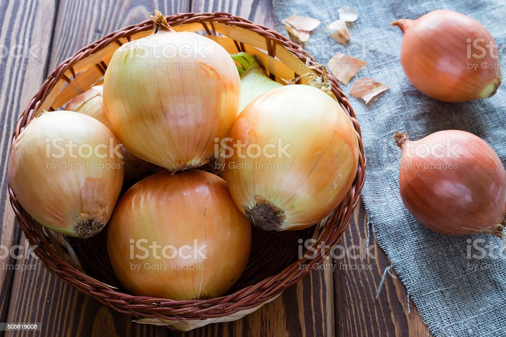 onions in a basket on a napkin closeup stock photo