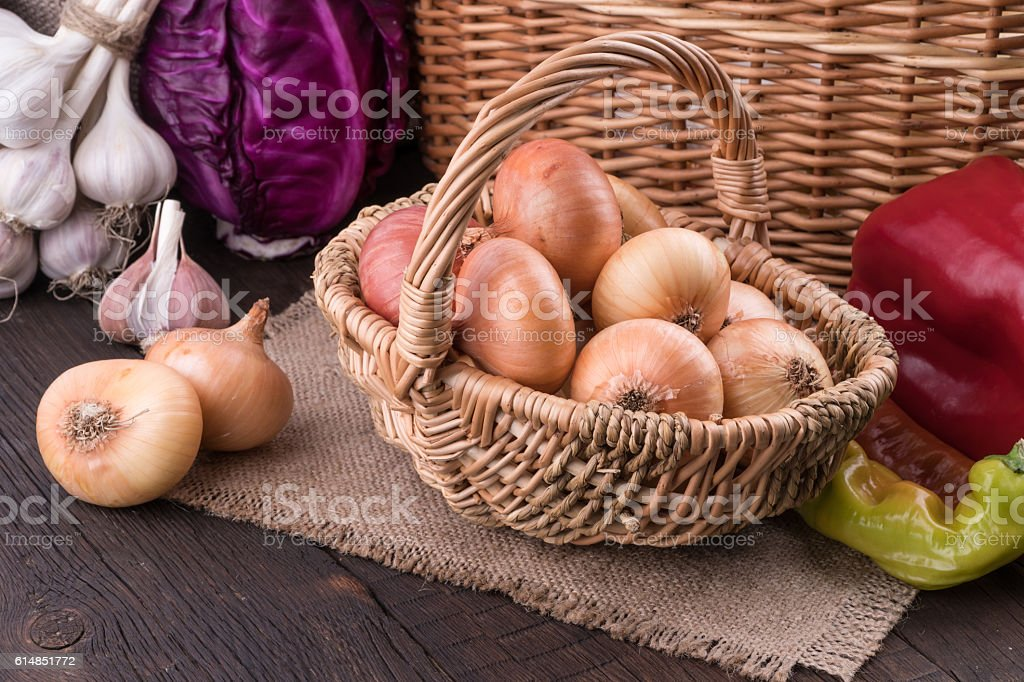 Onions in a wicker basket on old wooden table. stock photo