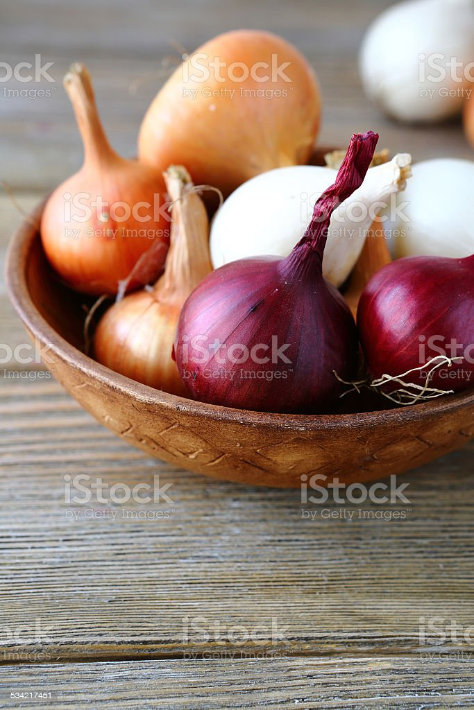 Onions in a wooden bowl stock photo