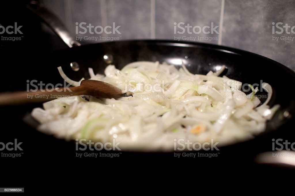 onions in frying pan stock photo