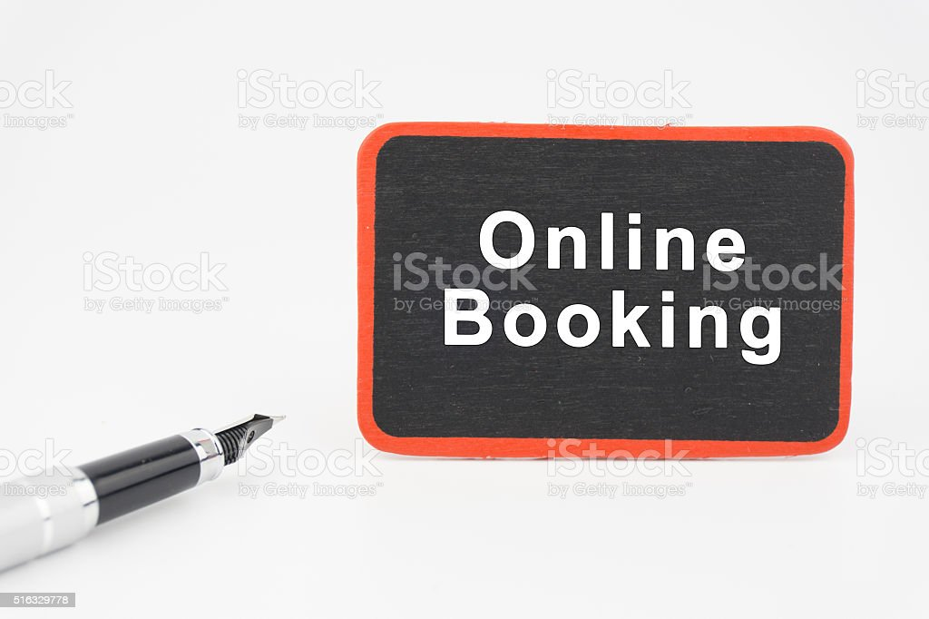 Online Booking on mini blackboard  with pen over white background stock photo