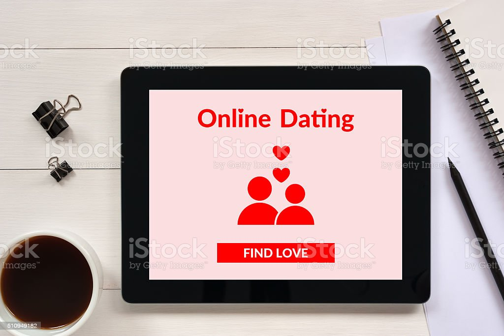 Online dating app mock-up on tablet screen with office objects stock photo