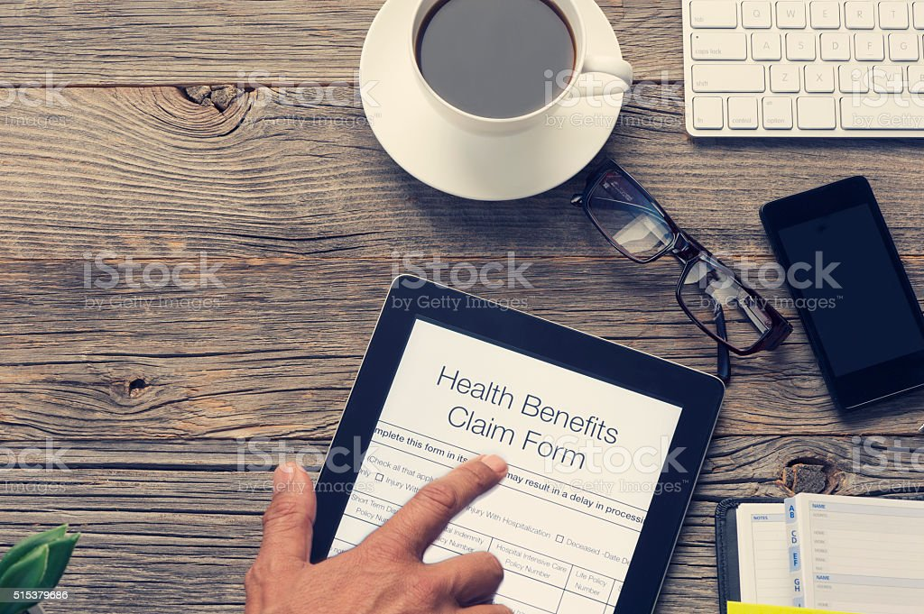 Online health benefits claim form with touching finger. stock photo